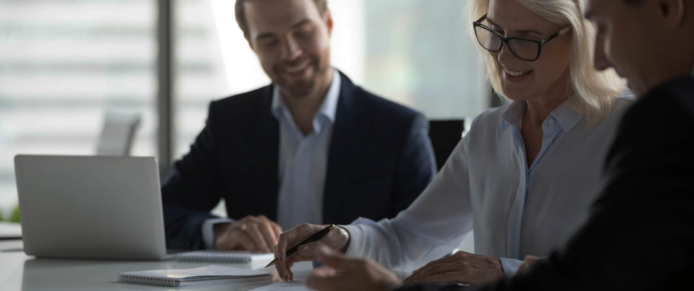 Smiling middle aged businesswoman signing paper contract at group meeting